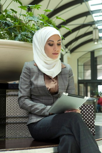 Young arab woman with digital tablet sitting at the shopping mall. : Stock Photo
