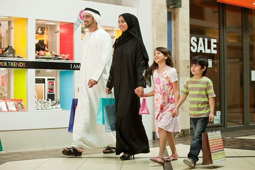 Arab family holding hands while walking in the shopping mall. : Stock Photo