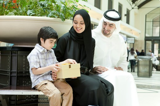 Stock Photo: 4305R-1322 Arab family sitting at the shopping mall, parents giving gift to their son.