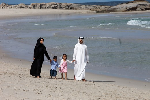 Stock Photo: 4305R-1343 Arab family holding hands while walking at the beach.