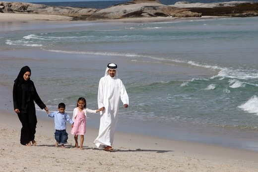 Stock Photo: 4305R-1345 Arab family holding hands while walking at the beach.