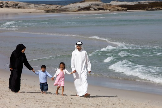 Stock Photo: 4305R-1346 Arab family holding hands while walking at the beach.