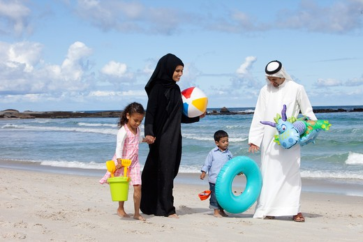 Arab family holding hands while walking at the beach. : Stock Photo