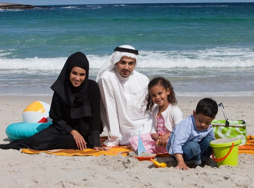 Arab family playing on the sand at the beach, smiling. : Stock Photo