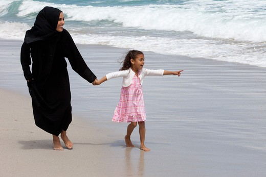 Arab mother and daughter holding hands while walking at the beach, girl pointing. : Stock Photo