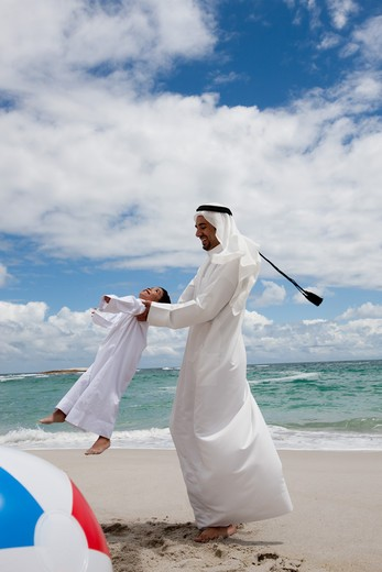 Arab father spinning around his son at the beach. : Stock Photo