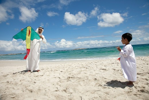 Stock Photo: 4305R-1558 Arab father and son with kite walking at the beach.