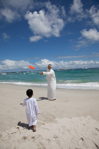 Arab father and san playing frisbee at the beach. : Stock Photo