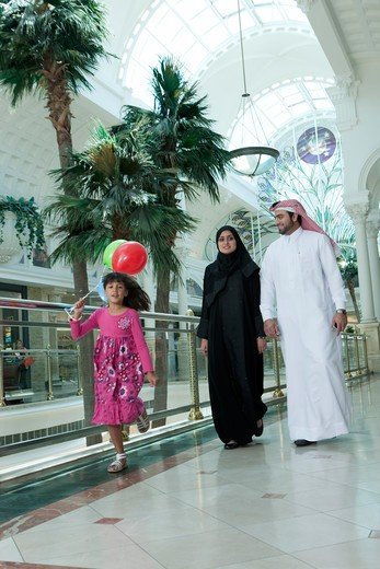 Arab family in shopping mall, girl running with balloons. : Stock Photo