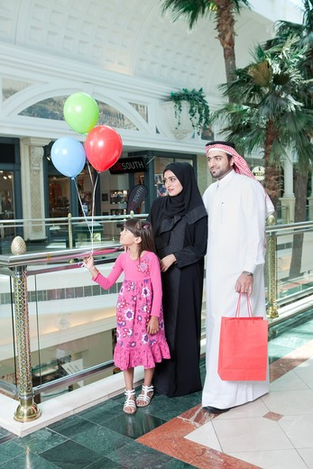 Arab family in shopping mall, girl holding balloons. : Stock Photo