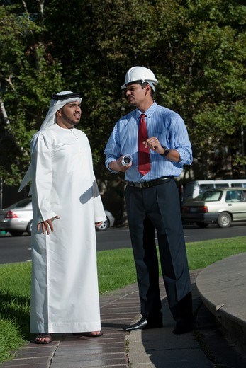 Stock Photo: 4305R-1736 Arab businessman and architect talking and standing on street.