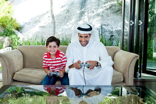 Stock Photo: 4305R-1817 Arab father and son playing video game together.