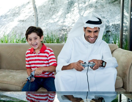 Stock Photo: 4305R-1820 Arab father and son playing video game together.