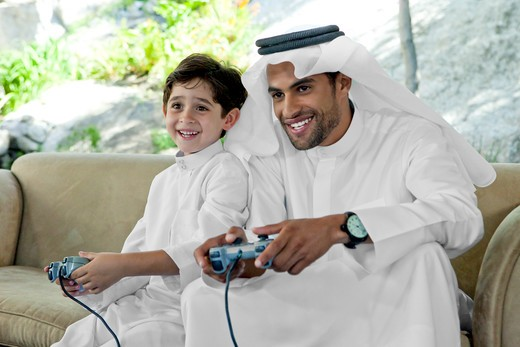Arab father and son playing video game together. : Stock Photo