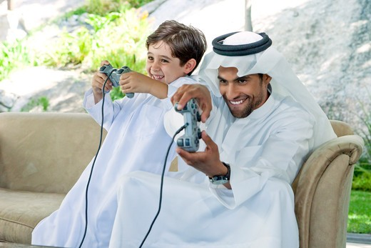 Stock Photo: 4305R-1835 Arab father and son playing video game together.