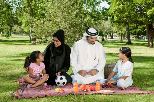Arab family picnic in the park. Parents talking to their children. : Stock Photo