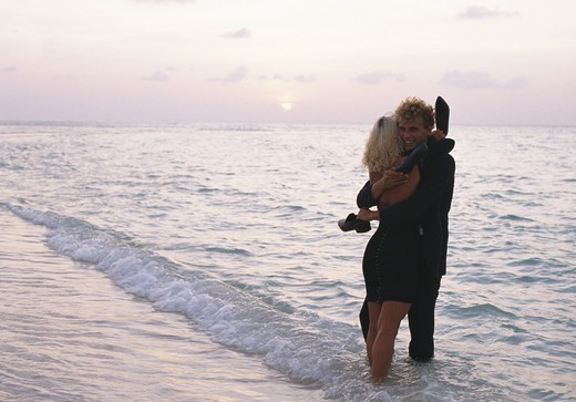 Stock Photo: 4306R-10793 Young couple huging at the water?s edge, Kuredo, Maldives.