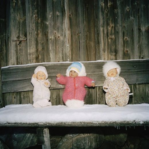 Three dolls sitting on a bench, Roslagen, Sweden. : Stock Photo