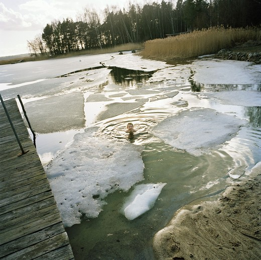 Stock Photo: 4306R-10964 Boy swimming in cold water, surrounded by ice floe, Trosa, Sweden.
