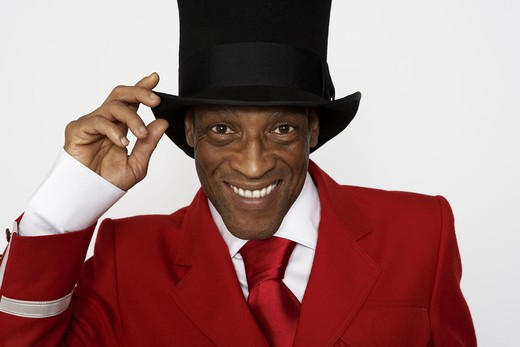 A smiling man wearing a hat and a red suit. : Stock Photo