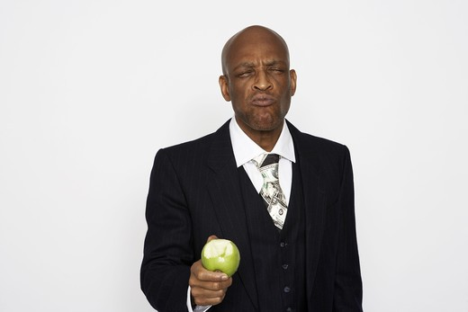 A middle aged man wearing a suit eating an apple. : Stock Photo