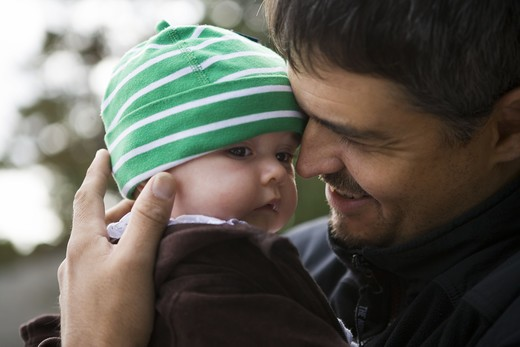 A father holding a little baby, Sweden. : Stock Photo