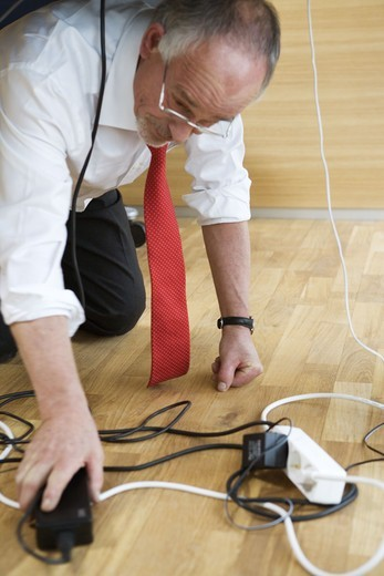 A buissnes man having problems with wires under a table. : Stock Photo