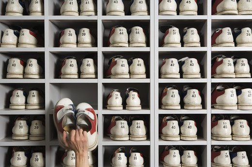 Hand picking shoes on shelves in a bowling alley. : Stock Photo