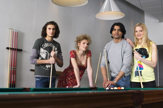 Four people standing by a pool table. : Stock Photo