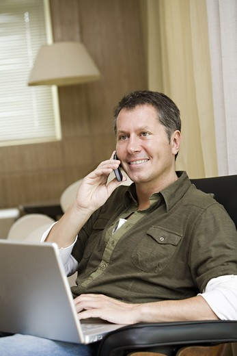 Stock Photo: 4306R-12176 Scandinavian man with a laptop using his mobile phone, Brazil.