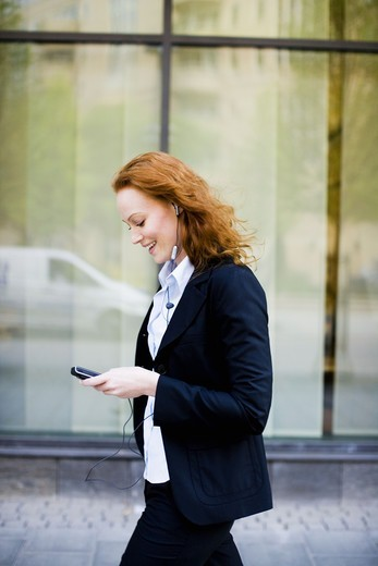 Smiling woman talking in her cellphone, Stockholm, Sweden. : Stock Photo