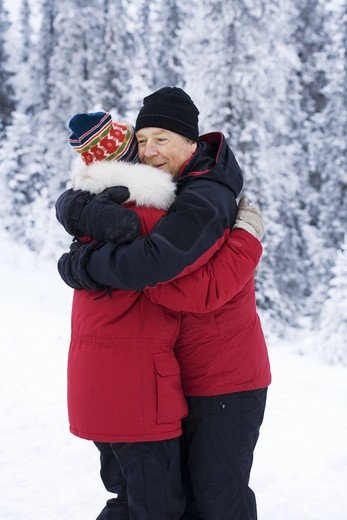 A middle aged couple hugging in the snow, Sweden. : Stock Photo