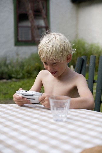 Stock Photo: 4306R-13793 A boy using a gameboy, Gotland, Sweden.