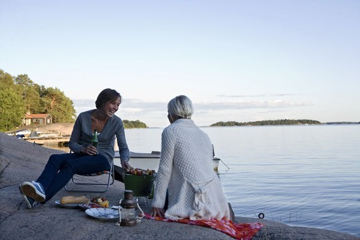 Two women having a picnic by the sea in the archipelago of Stockholm, Sweden. : Stock Photo
