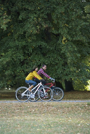 A woman and a man riding a bike an autumn day, Sweden. : Stock Photo