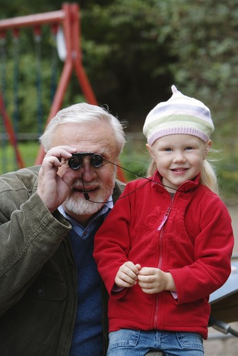 Stock Photo: 4306R-14778 Grandfather and grandchild looking through binoculars, Sweden.