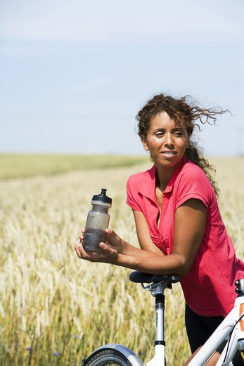 A woman with a water bottle and a bicycle, Sweden. : Stock Photo