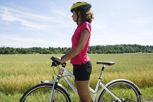 A woman riding a bike in the countryside, Sweden. : Stock Photo
