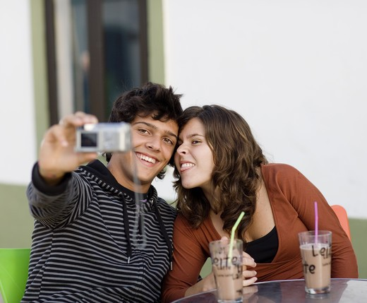 Stock Photo: 4306R-15280 A young couple sitting at a cafe holding a camera, Portugal.