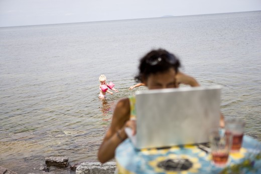 Stock Photo: 4306R-15502 Woman using a laptop on the beach, Oland, Sweden.