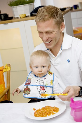 Stock Photo: 4306R-15974 A father feeding his baby, Sweden.