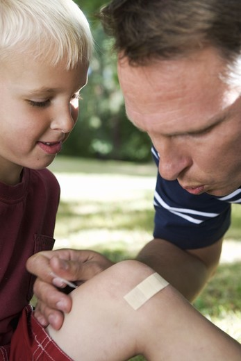 A father putting on a plaster on the knee of his son, Sweden. : Stock Photo