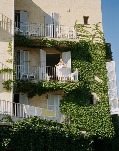 Stock Photo: 4306R-16124 A woman on a balcony, France.