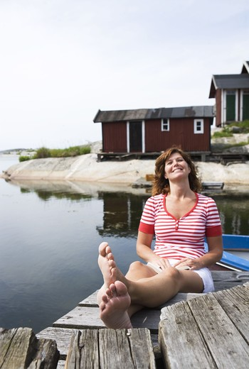 Stock Photo: 4306R-16182 A woman sitting on a jetty in the archipelago of Stockholm, Sweden.