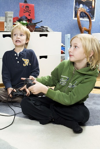 Stock Photo: 4306R-16420 Two Scandinavian boys playing video games, Sweden.