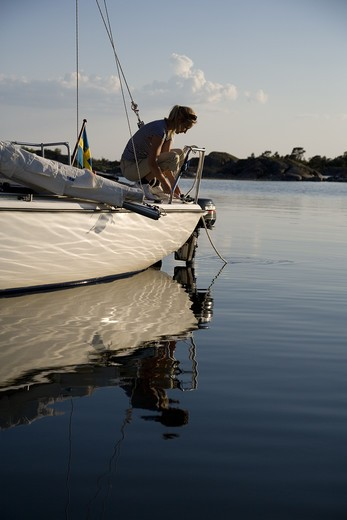 Stock Photo: 4306R-16451 A woman sitting on a sailing-boat, Ostergotland, Sweden.
