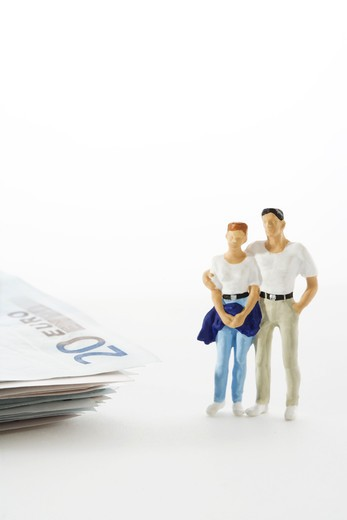Figures in the shape of a couple standing next to a bunch of money. : Stock Photo