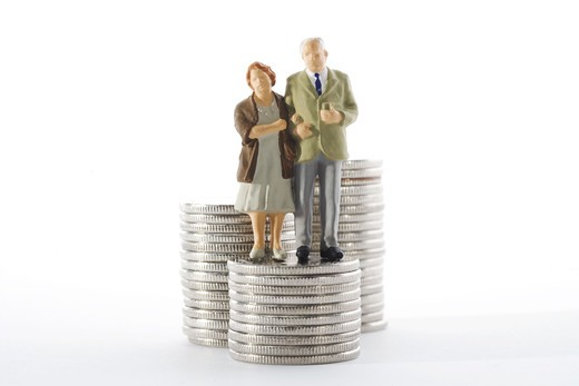 Stock Photo: 4306R-16593 Figures in the shape of a senior couple standing by coins.