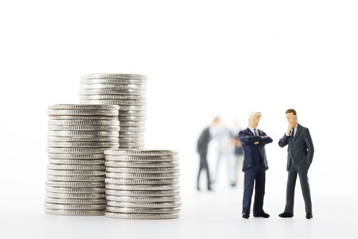 Figures in the shape of business men standing next to a pile of coins. : Stock Photo