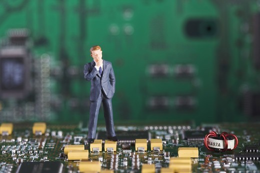 Figure in the shape of a business man standing in a printed circuit card. : Stock Photo